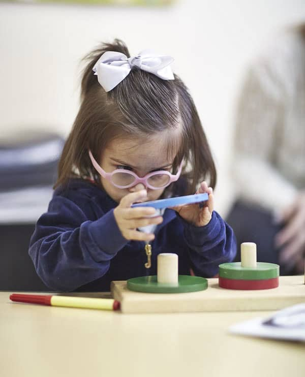 Preschool girl with glasses placing wooden circles on peg