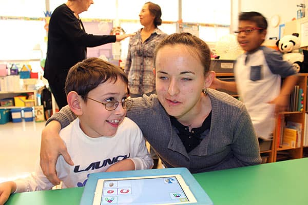 A college-aged woman who is visually impaired puts her arm around a kindergarten boy with glasses, who smiles at his iPad in his classroom
