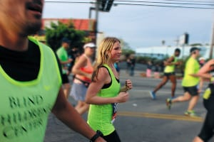 A young woman runs a marathon in a neon green tank top that reads
