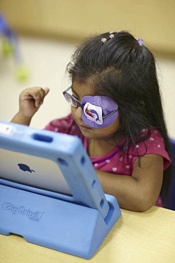 Kindergarten girl wearing glasses and an eye patch and reading on an iPad in a classroom