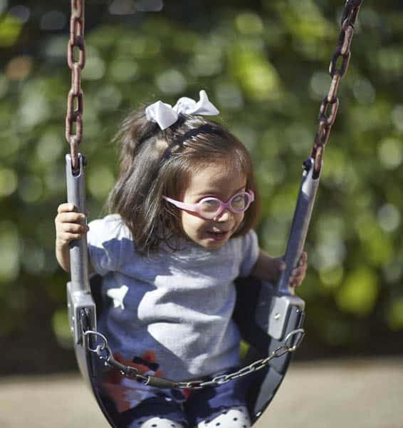 A preschool girl with glasses swinging on a swing