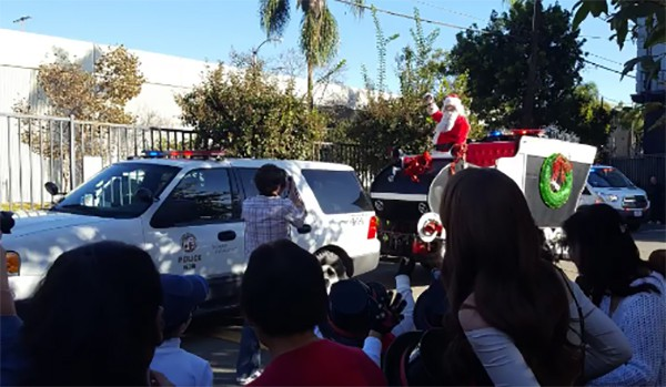 A Los Angeles Police Department officer dressed as Santa rides in a sleigh pulled by a police car in the BCC parking lot