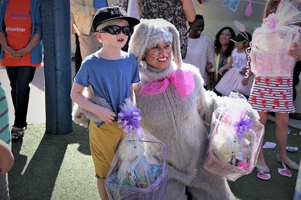 A young boy with albinism wearing sunglasses smiles holding an Easter basket next to a woman dressed as the Easter bunny