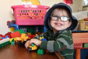 Boy with glasses playing with toy cars and smiling in a classroom