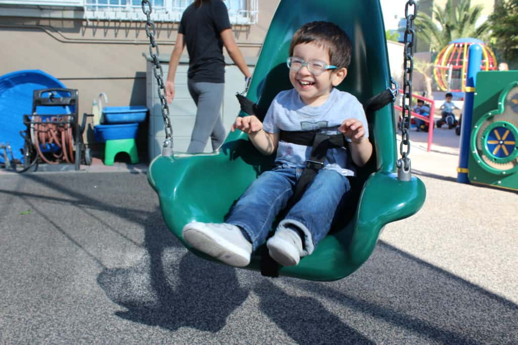 Preschool boy with glasses laughing on a swing outside