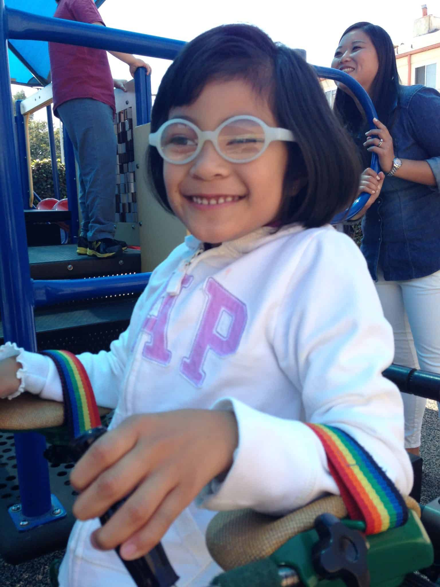 A young girl with glasses and a walker smiles on the playground