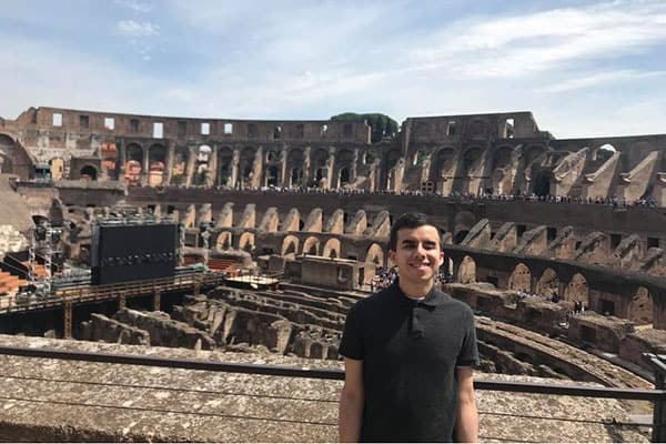A young man smiles in front of the Coliseum in Rome