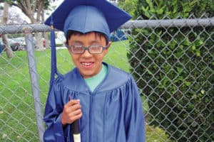 A kindergarten boy with glasses and a white cane smiles in a blue graduation cap and gown outside