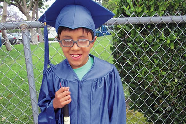 A young boy with glasses and a white cane stands outside in a blue graduation cap and gown