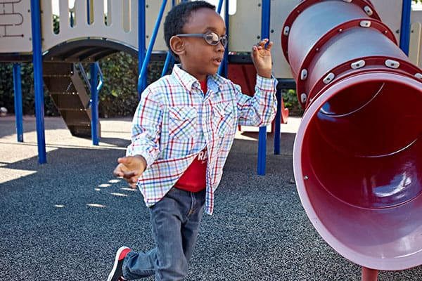 A young boy with glasses runs in front of a playground