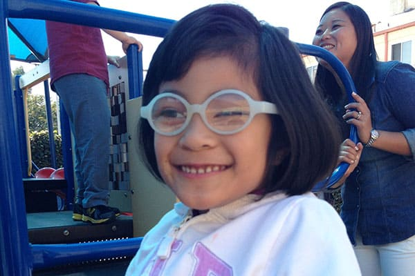 A young girl with glasses smiles on the playground