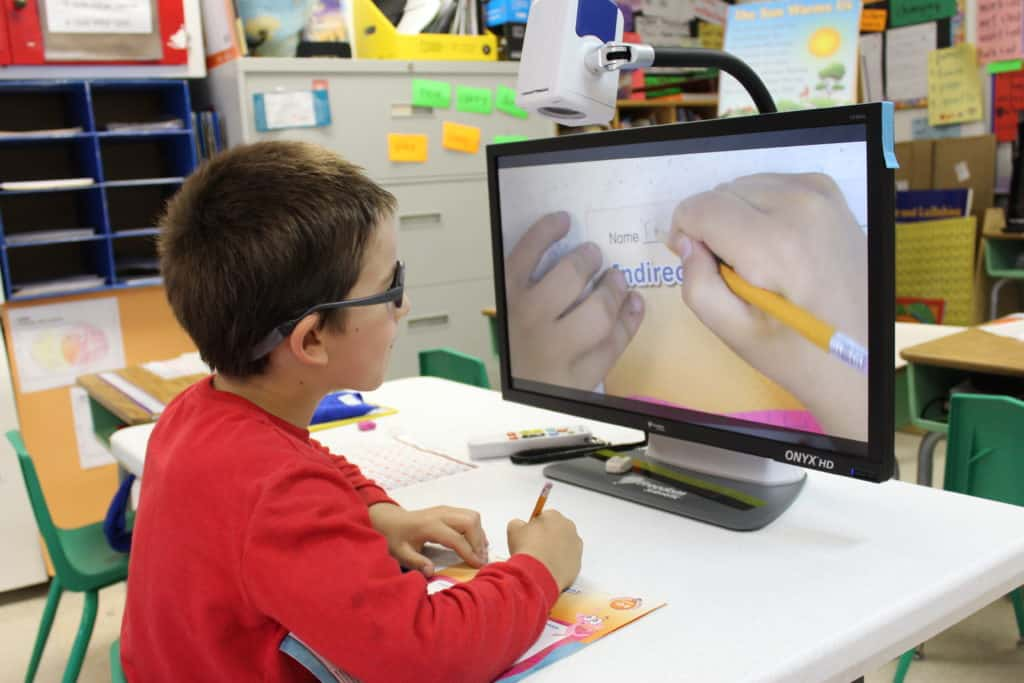 A kindergarten boy uses a visual magnification device to write his name on a worksheet in his classroom