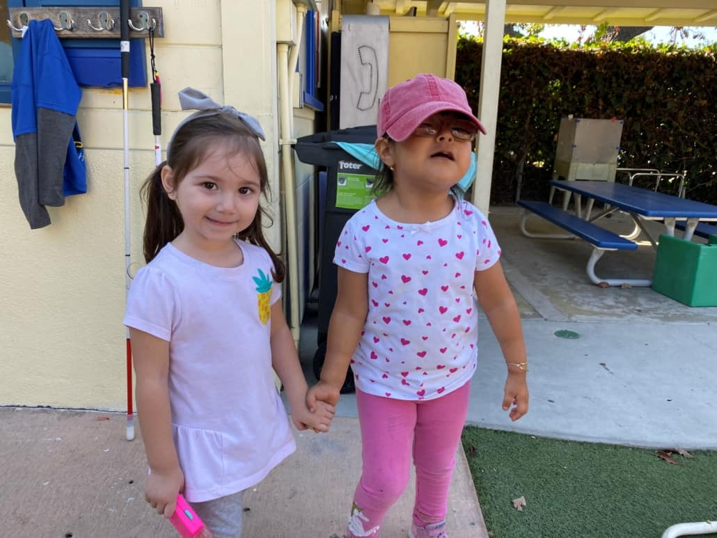 A preschool girl with glasses holds hands with another preschool girl standing on the playground
