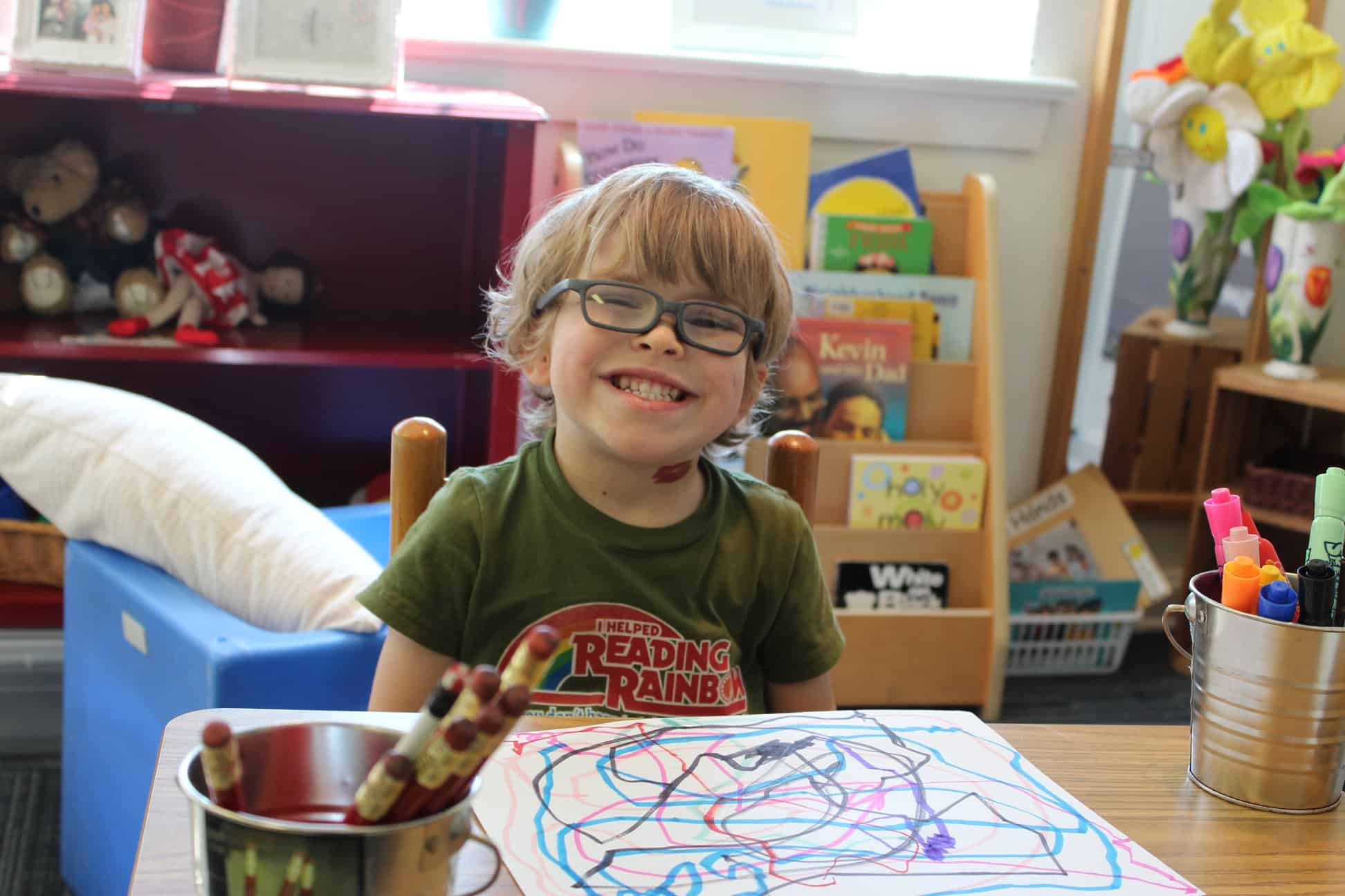 A preschool boy wearing glasses sits and smiles at his desk in his classroom
