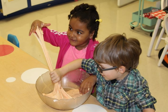 A preschool boy with glasses and a preschool girl reach into a bowl and stretch out orange slime in their classroom