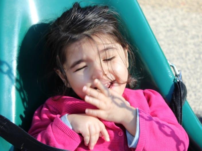 A preschool girl smiles on a swing outside