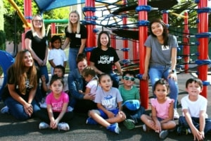 Six adult volunteers smile with 8 kindergarten children on the playground
