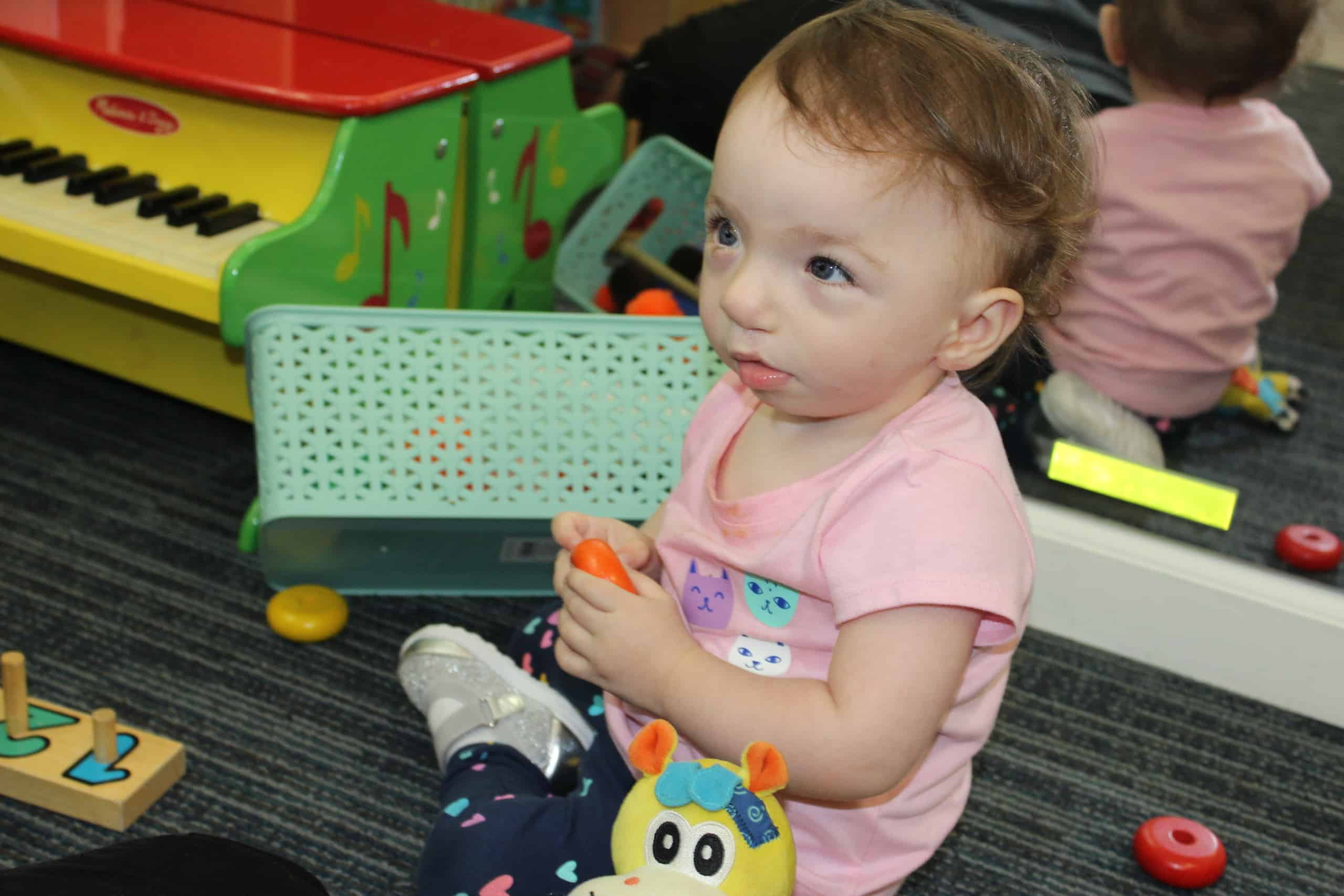 An infant girl sits on the classroom floor playing with a bright orange toy