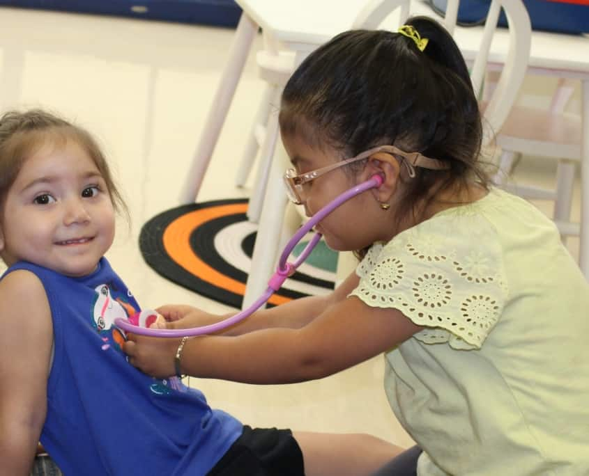 A preschool girl with glasses uses a play stethoscope to play doctor with her smiling friend