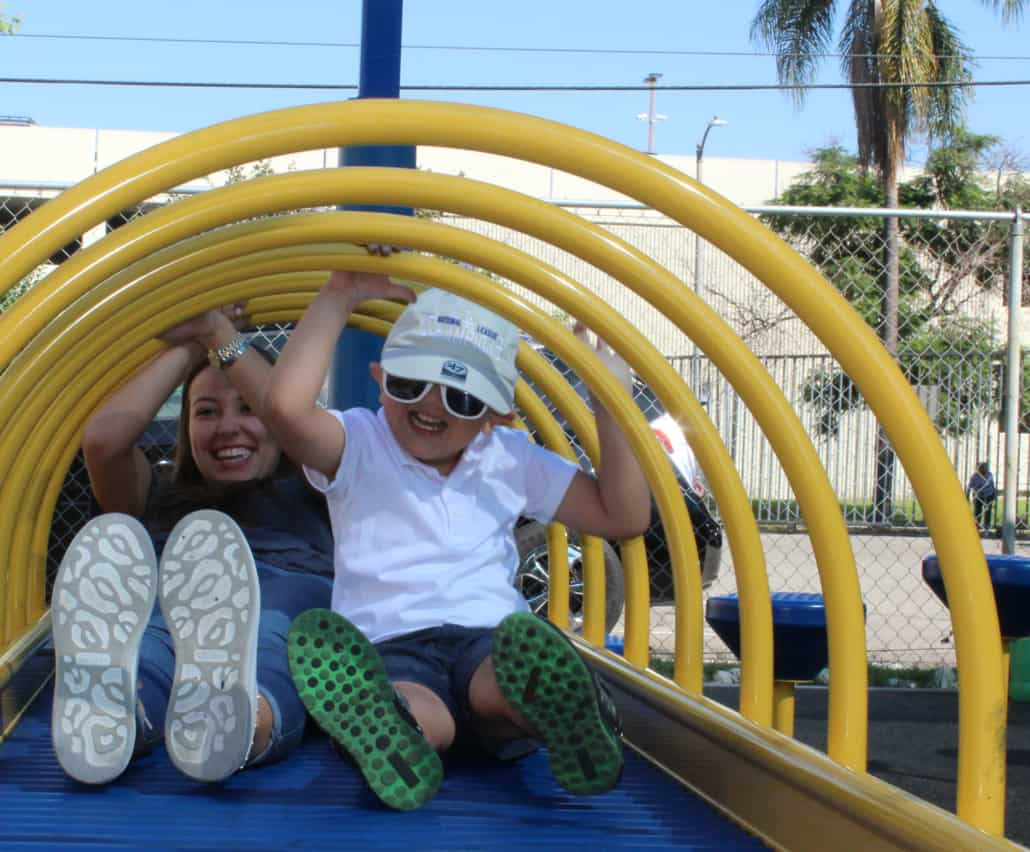 A preschool boy with glasses and a college-aged volunteer slide through a piece of playground equipment while smiling