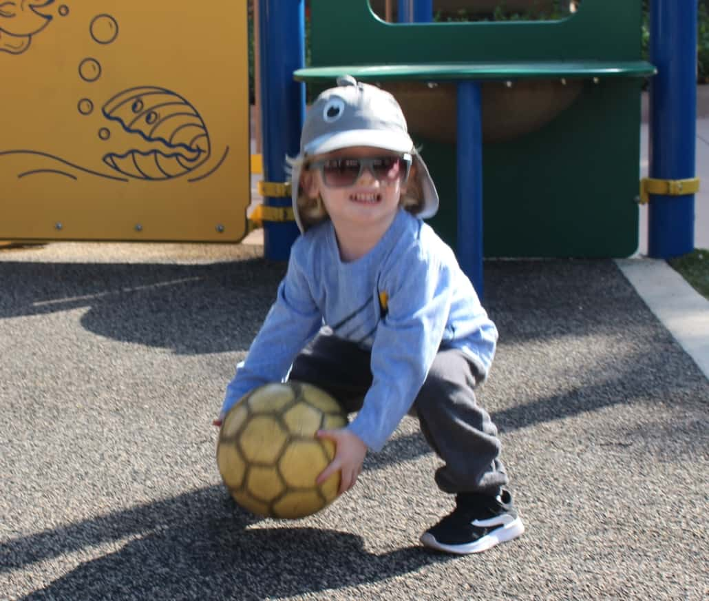 A preschool boy with albinism who is wearing sunglasses smiles while picking up a soccer ball outside