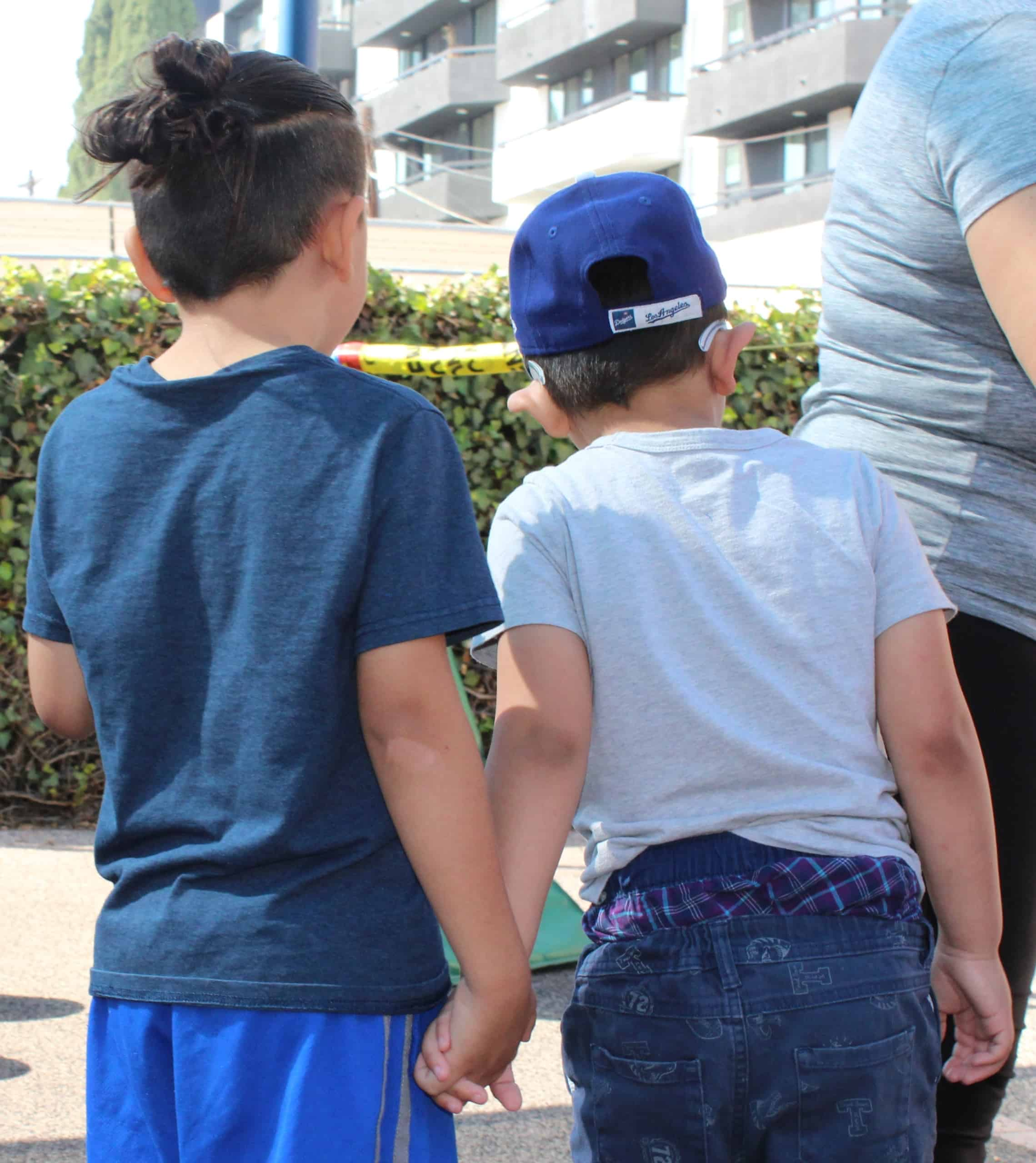 Two kindergarten boys hold hands on the playground