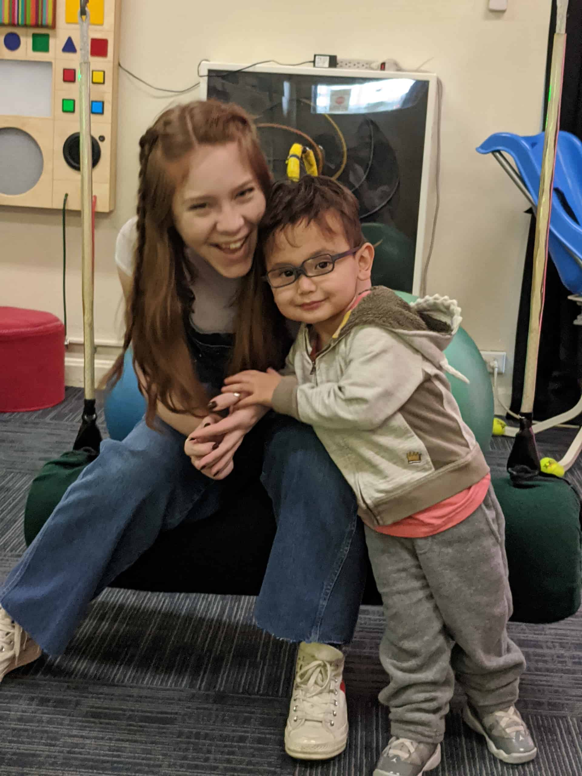 A preschool boy with glasses hugs a teacher sitting on a swing in the Therapeutic Learning Center
