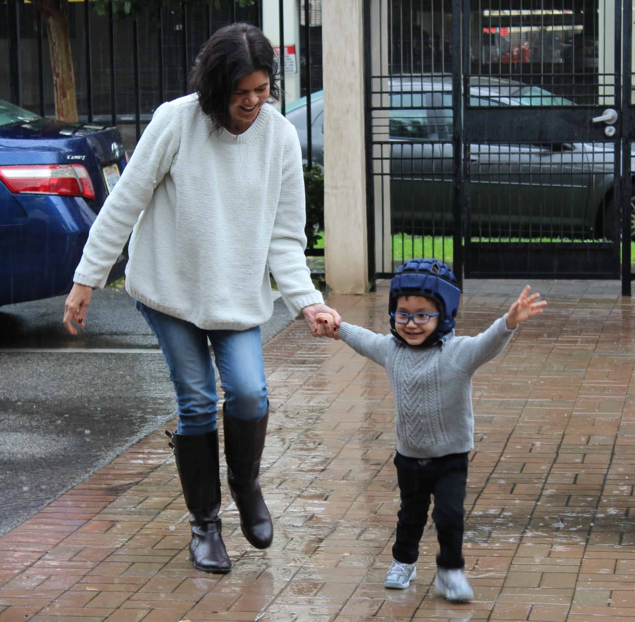A specialist holds the hand of an excited preschool boy with glasses as they splash in puddles in the BCC parking lot