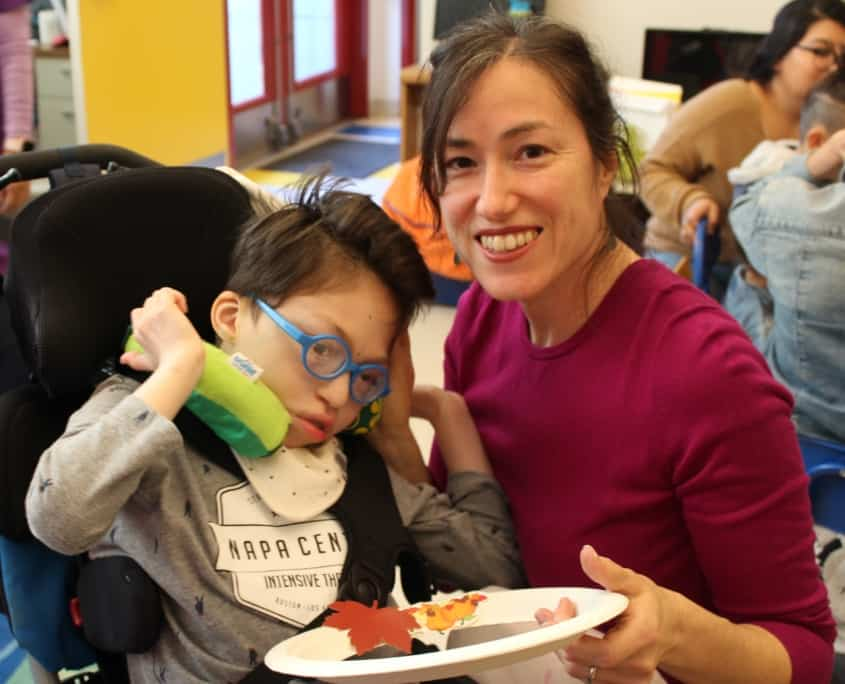 A mother holds a craft with her kindergarten son, who wears glasses and is in a wheelchair