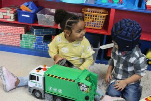 A preschool girl and a preschool boy with glasses play with a toy garbage truck in a classroom