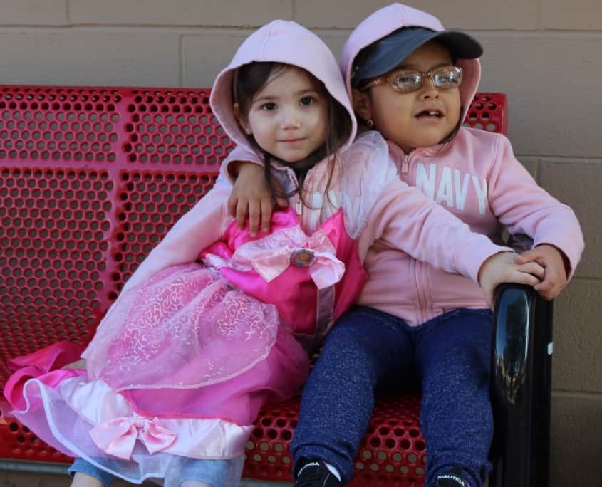 A preschool girl with glasses hugs a preschool girl dressed in a princess costume on a bench outside