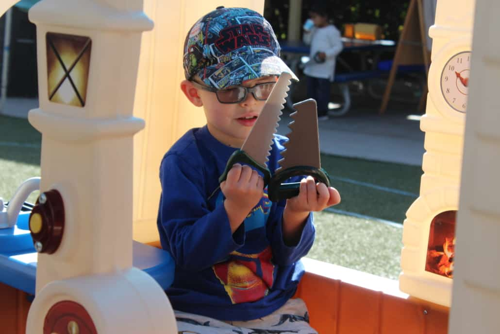 A preschool boy with glasses looks at two plastic saws while sitting in a playhouse