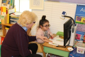 A teacher of the visually impaired guides a kindergarten girl with glasses in using her visual magnification device to read a book