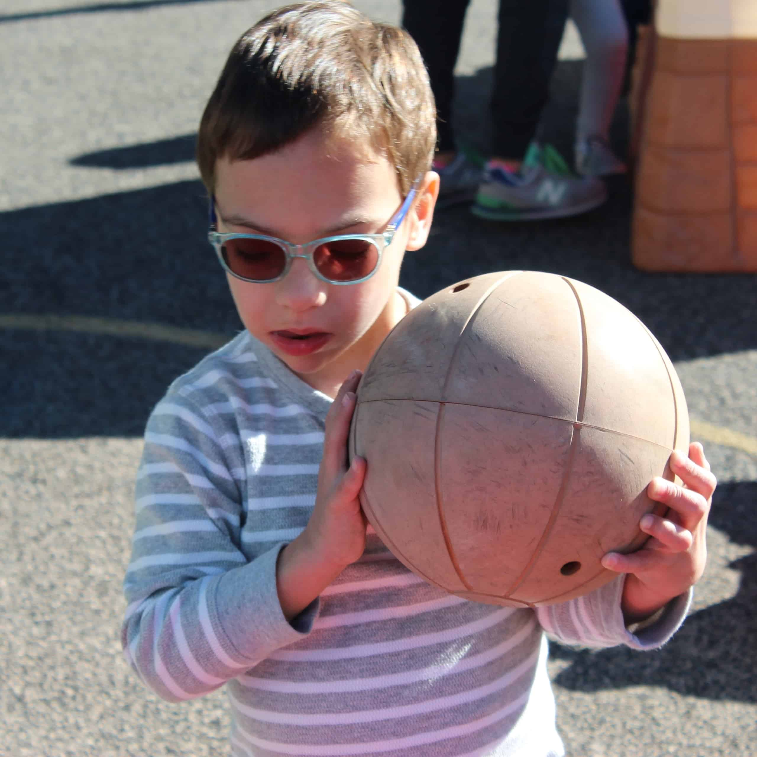 A preschool boy with glasses holds a beeping basketball close to his face