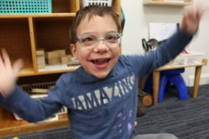 A preschool boy with glasses waves his hands and smiles in his classroom