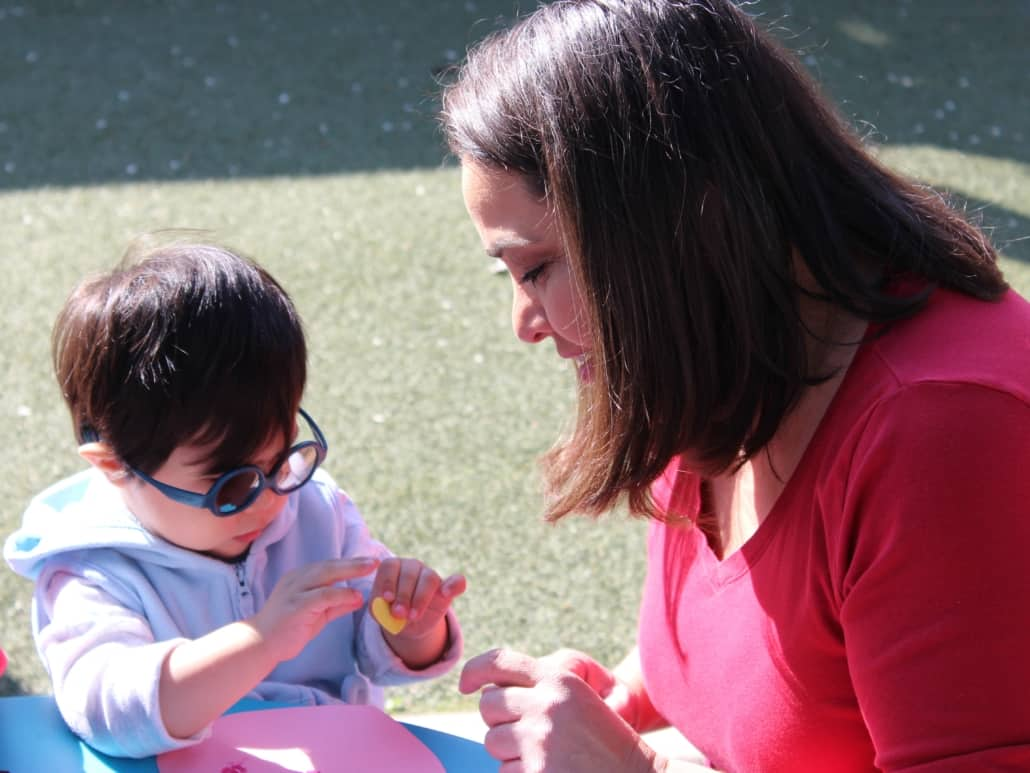 A toddler boy with glasses and his teacher do a craft project outside