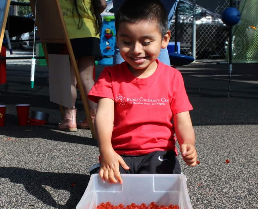 A preschool boy in a red Blind Children's Center t-shirt smiles at a plastic bin filled with red sensory beads on the playgrund