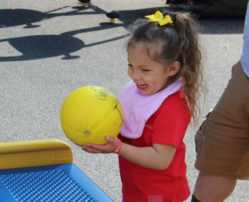 A kindergarten girl smiles while holding a yellow beeping ball on the playground