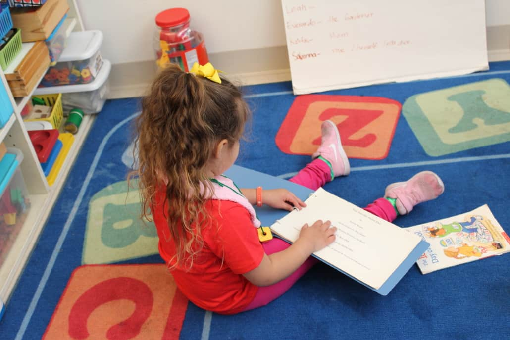 A preschool girl sits on the floor of her classroom reading a Braille book