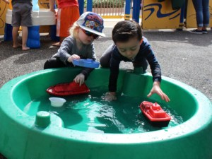 Two preschool boys play with plastic boats in a plastic pool on the playground