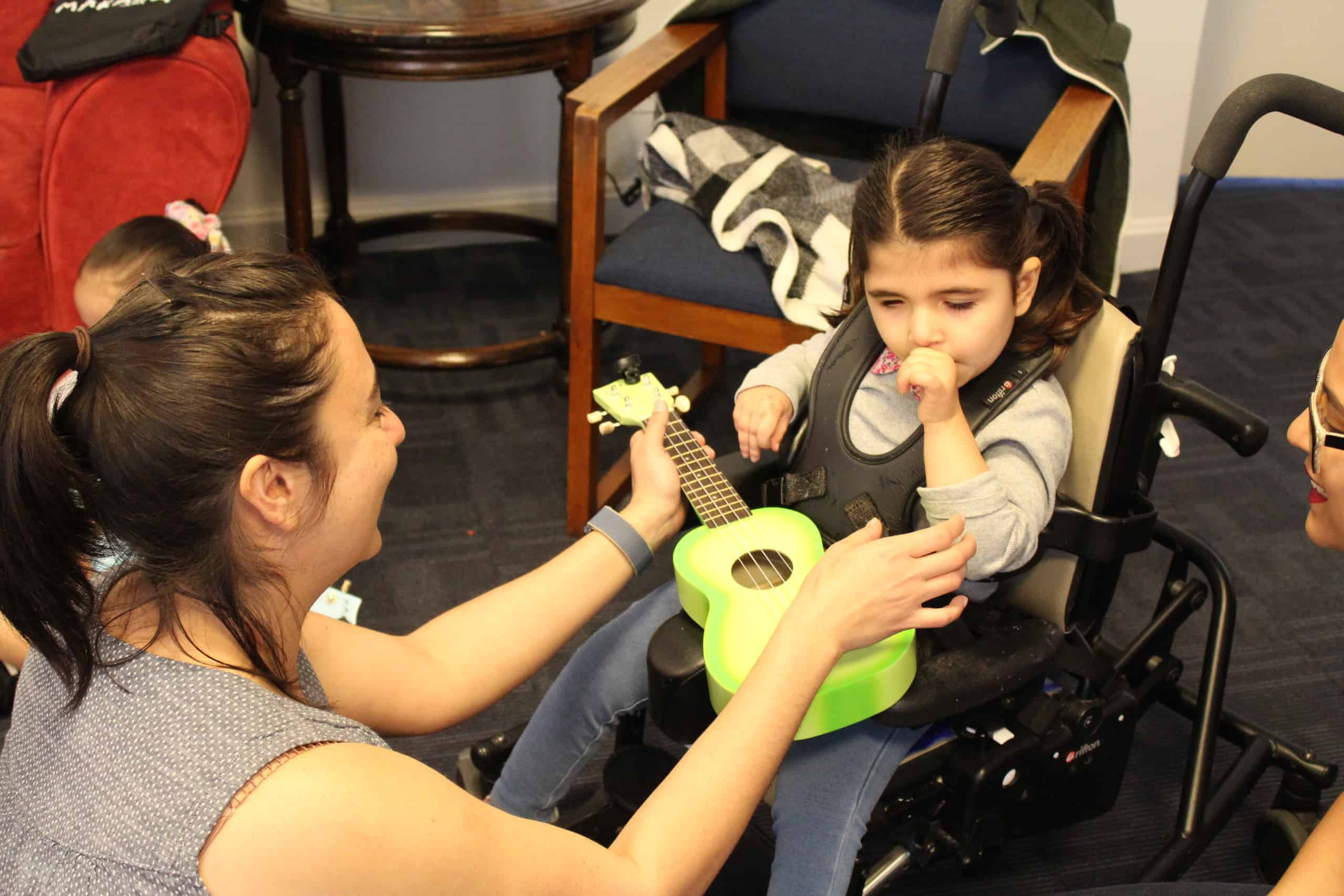 A specialist holds a green ukulele on the lap of a preschool girl in a wheelchair and encourages her to touch it