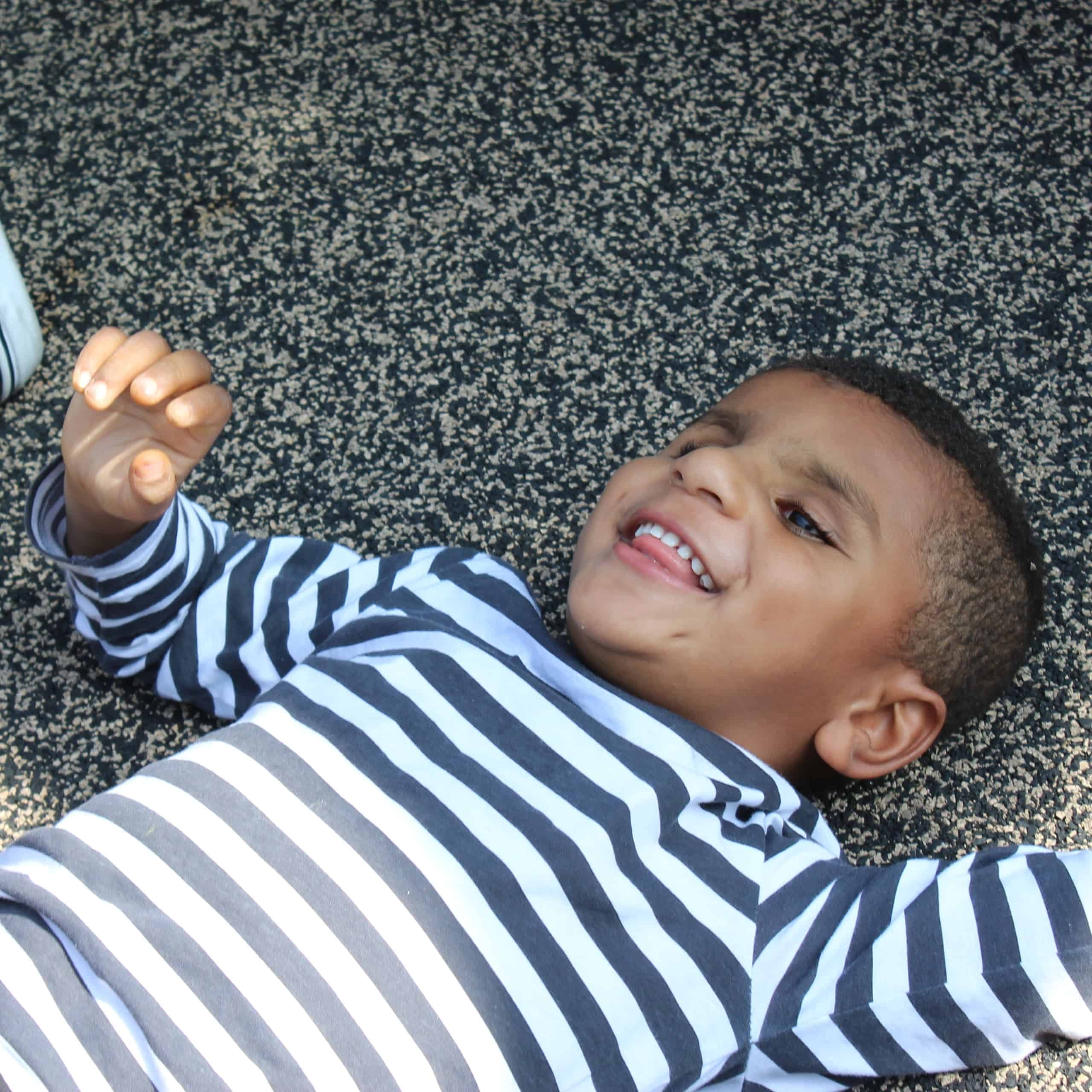 A preschool boy lays on the playground floor and smiles while waving his arms