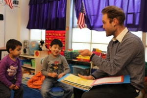 A man reads a book to two preschool boys in their classroom