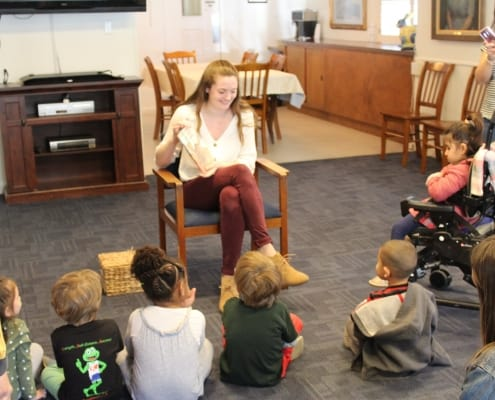 A college girl reads a book to a group of preschool children who are visually impaired in the BCC Living Room