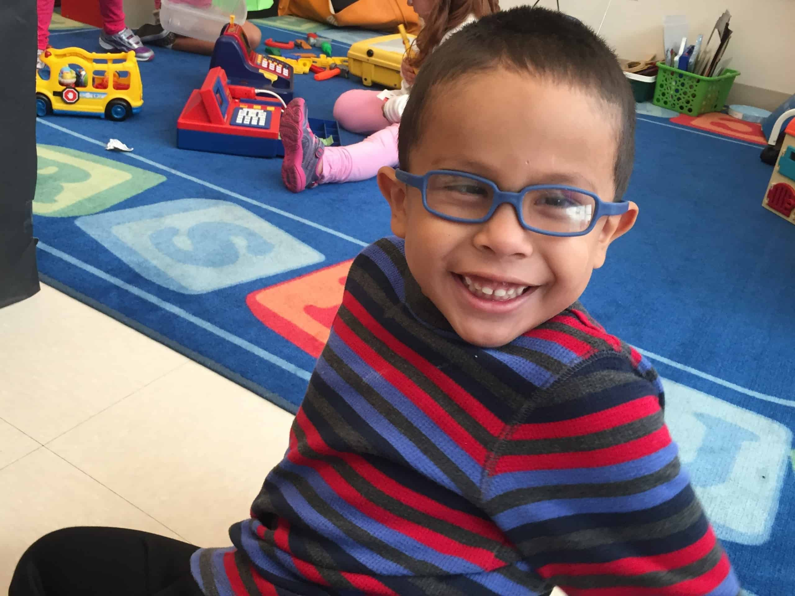 A young boy with glasses smiles at the camera and sits on the floor of his classroom