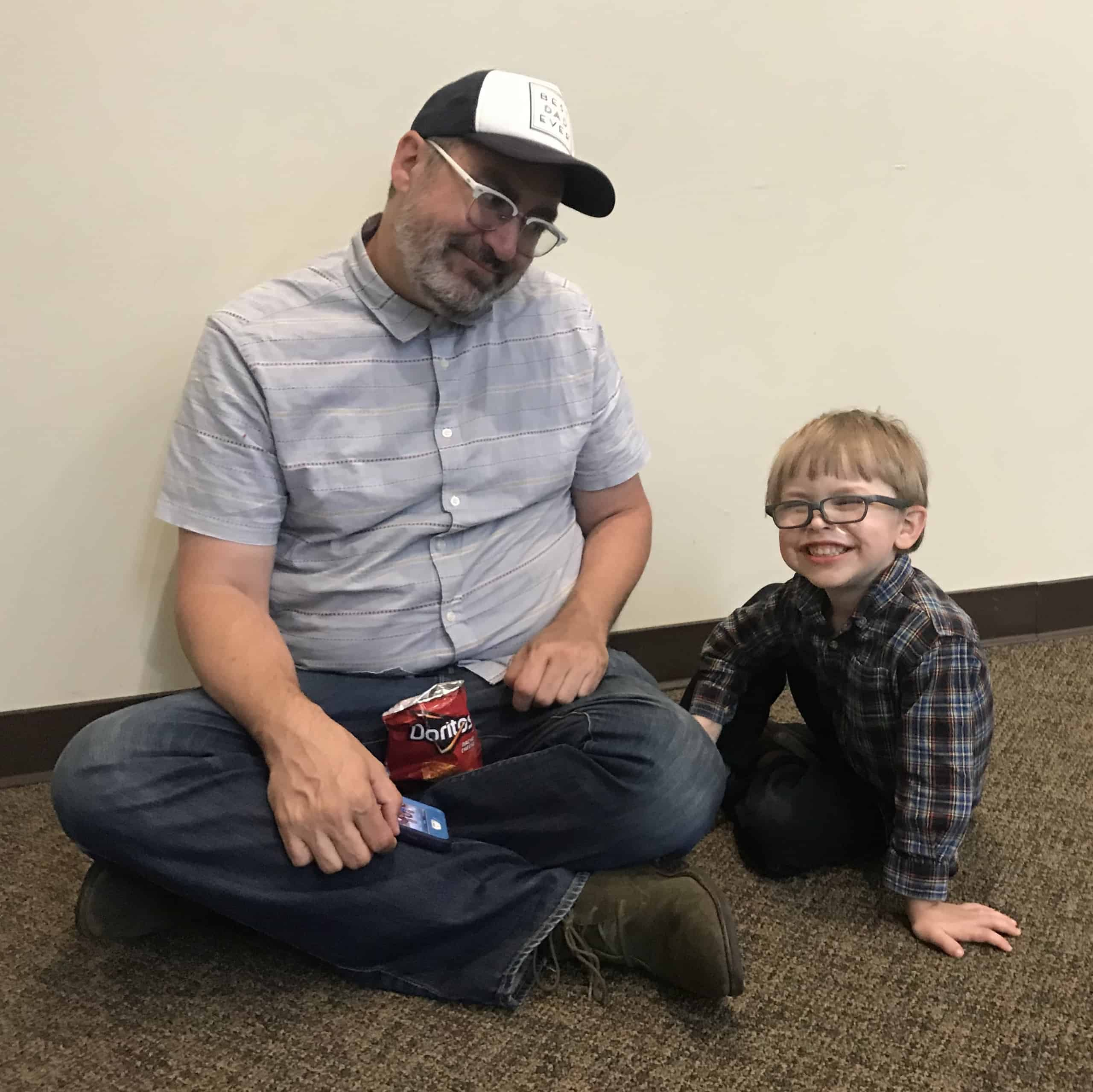 A man and a preschool boy with glasses sit on the floor, smiling