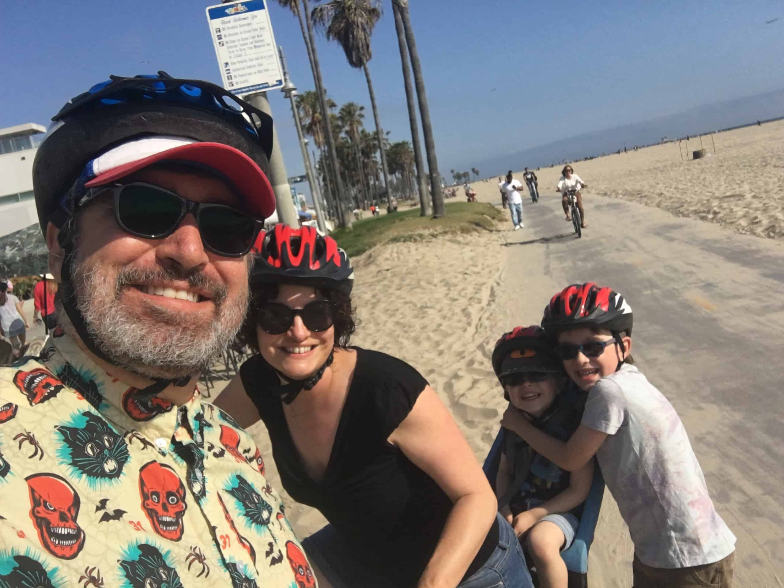A man, woman, and two hugging boys with glasses bike on a beach trail