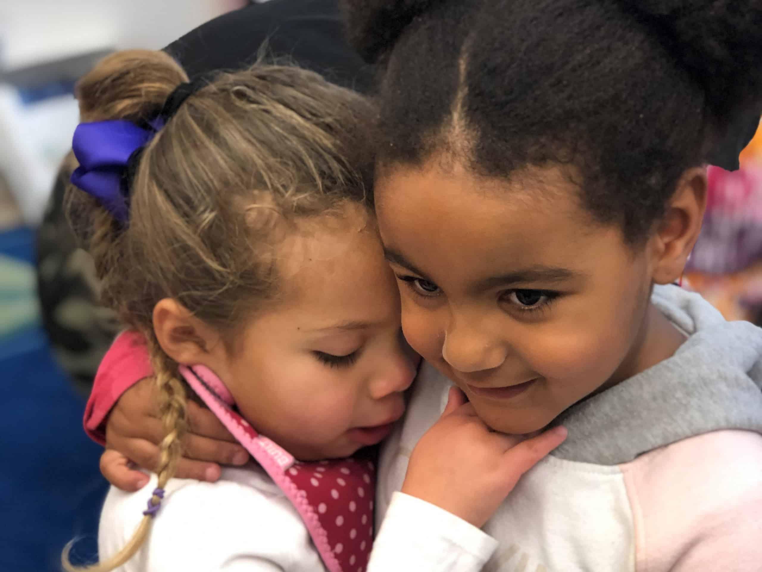 Two preschool girls hug inside