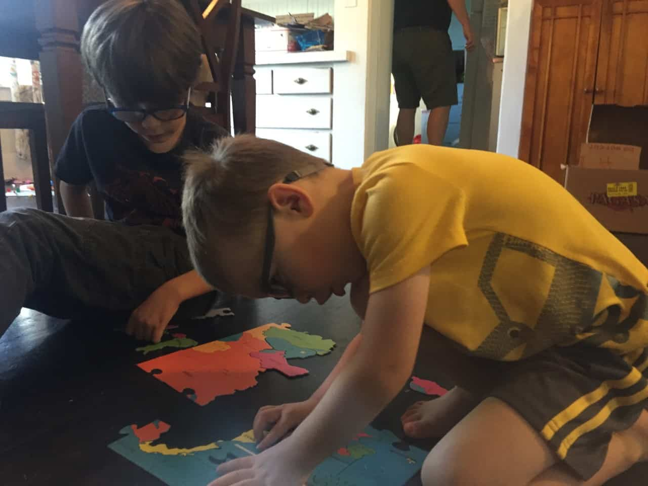Two boys with glasses do a puzzle on the floor